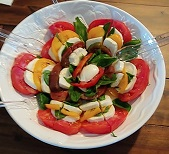 Large bowl of sliced tomatoes layered with slices of mozzarella and basil leaves